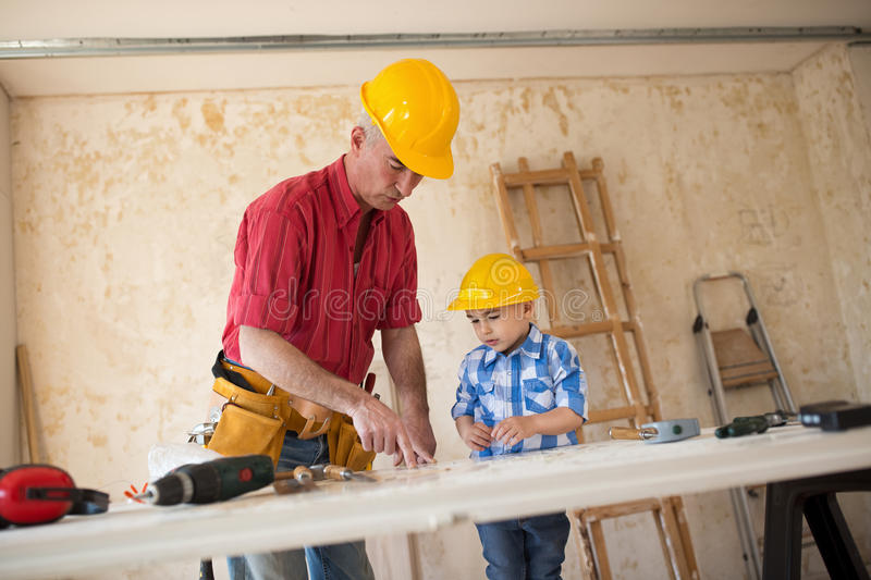 Worthy grandfather and grandson in a carpenter`s workshop stock photos