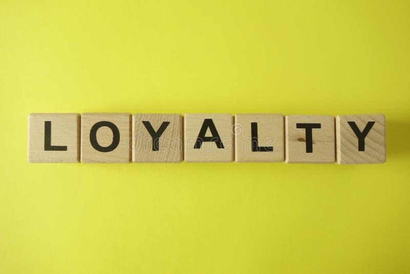 Wortloyalität von den hölzernen Buchstaben auf gelbem Hintergrund stockbild