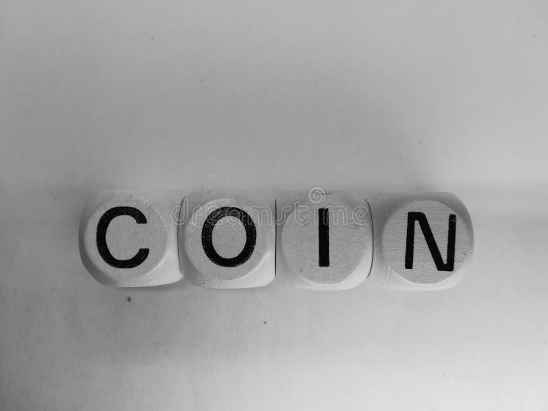 Wortmünze buchstabiert auf Würfeln stockfotografie