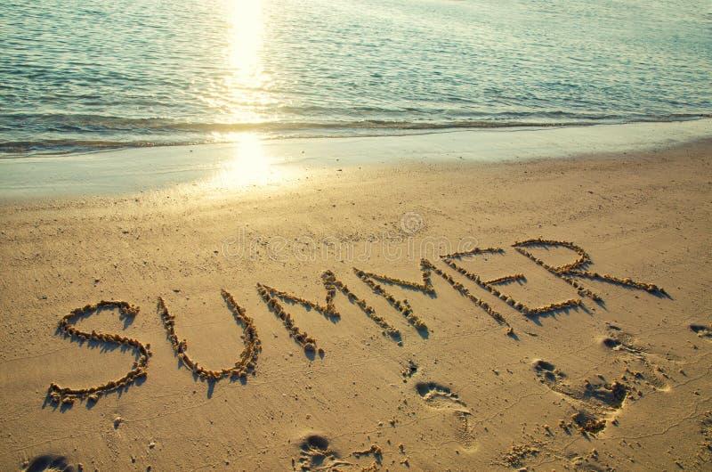 Wortsommer geschrieben auf wei?en Sandstrand Sommerferien, Reise und Ferienkonzept Abstrakter Seestrandhintergrund stockfotografie