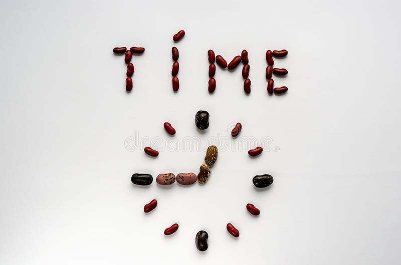 Wortzeit und -Ziffernblatt geformt aus bunten Gartenbohnen auf wei?em Hintergrund heraus Gesundes Essenkonzept stockbild
