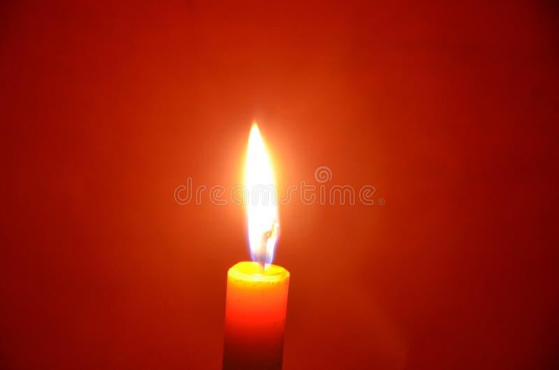 Wosk świeczki światło z czerwieni ubrań tłem w nocy obrazy stock