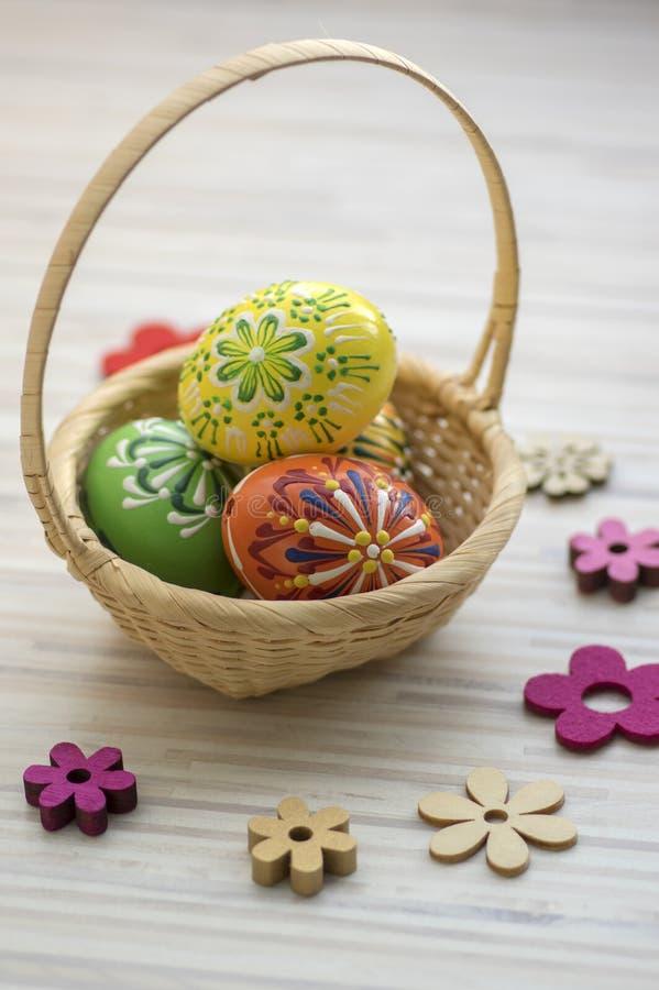 Wosk malował Wielkanocnych jajka w jasnobrązowym łozinowym koszu, drewniane kwiat dekoracje obraz stock