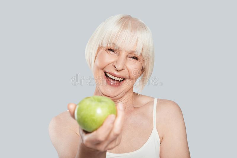 Would you like some?. Beautiful senior woman holding an apple and smiling while standing against grey background stock image