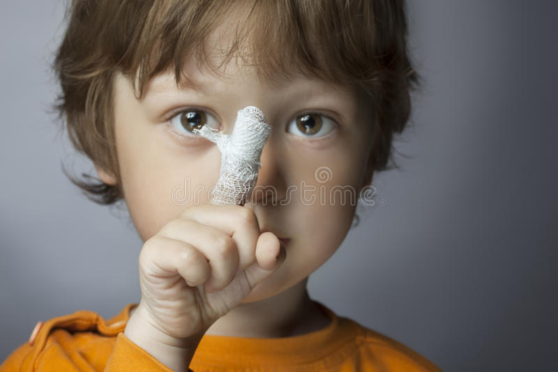 Wound, focus on finger. Boy with a bandaged wound on his finger (focus on finger royalty free stock images