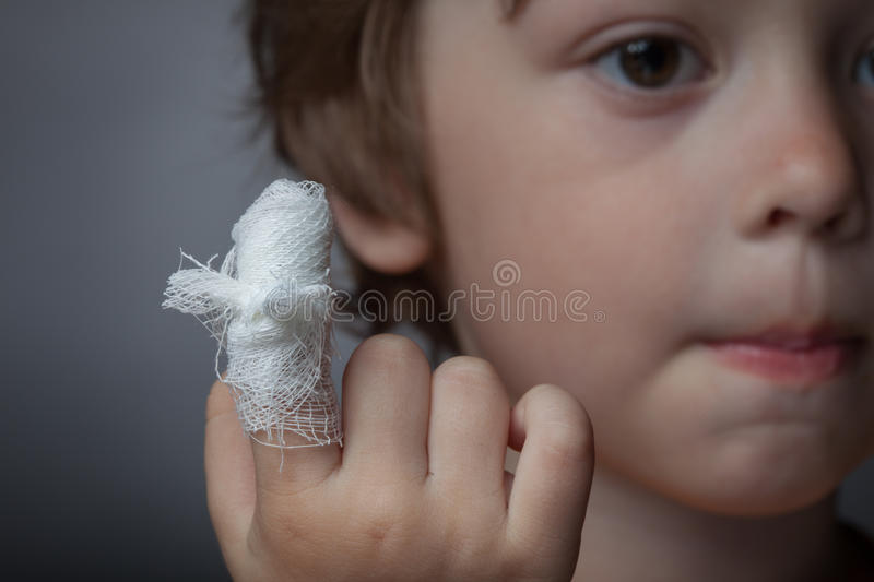 Wound, focus on finger. Boy with a bandaged wound on his finger stock photos