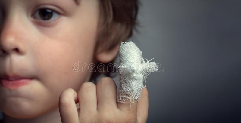Wound, focus on finger. Boy with a bandaged wound on his finger royalty free stock image