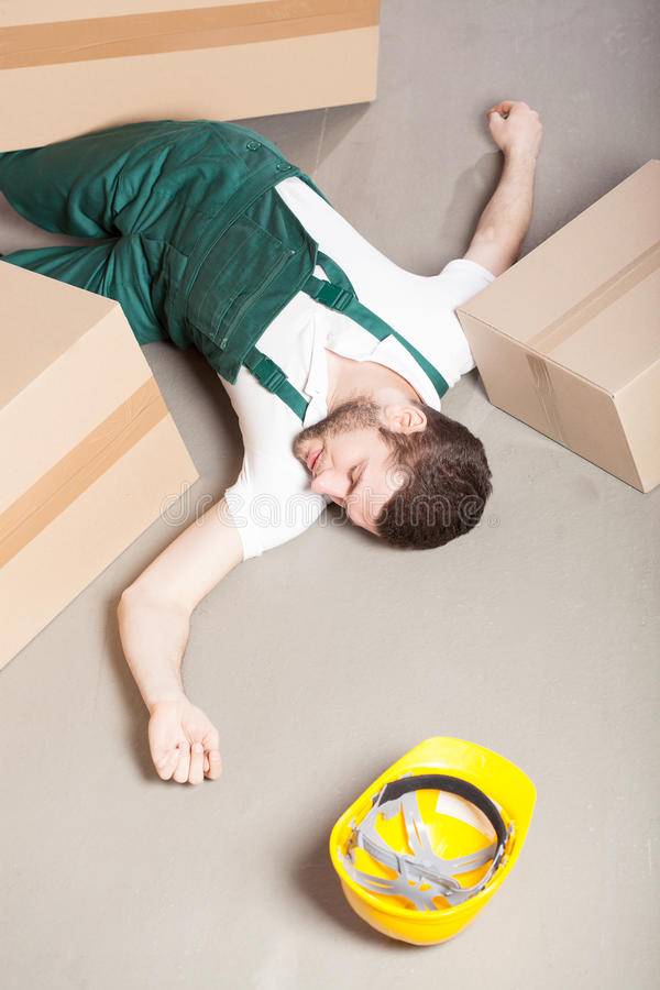 Wounded warehouse worker lying on the floor. Wounded warehouse worker lying unconscious on the floor after accident royalty free stock photo