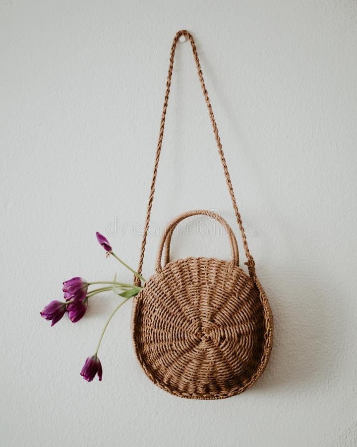 Woven bag with purple poppies royalty free stock photo