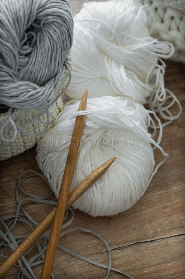 A woven basket with white and gray thread for knitting and knitting needles. White sweaters and yarn for knitting closeup. Winter royalty free stock photo