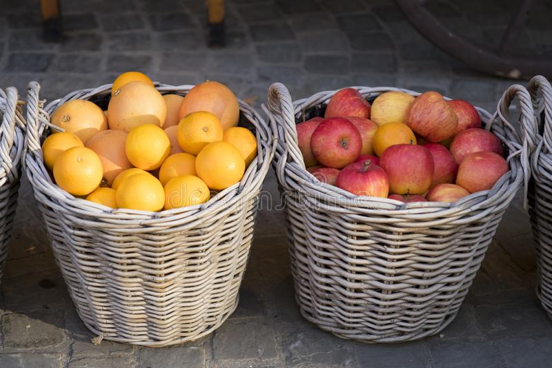 Woven baskets with red apples and oranges stock image