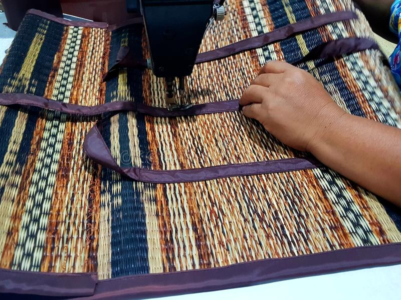Woven Reed Mats. Woven Reed Mats sewing by woman stock image