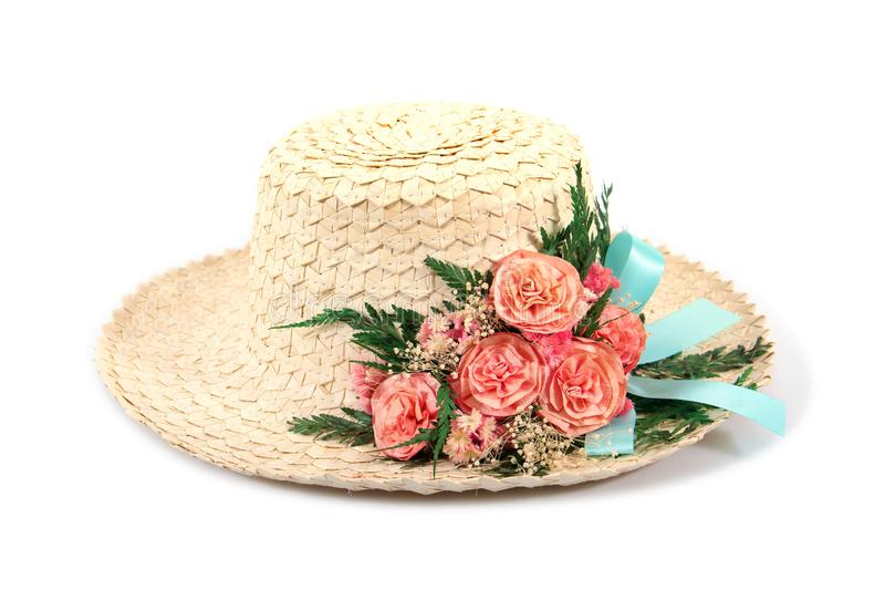 Woven woman hat with artificial rose flowers and leaves with blue ribbon isolated on white background stock photography