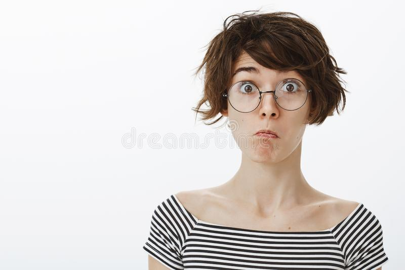 Wow, μη κακός είμαι εντυπωσιασμένου Πορτρέτο του χαριτωμένου ευτυχούς και αστείου κοριτσιού στα στρογγυλά γυαλιά που τραβούν το π στοκ εικόνα με δικαίωμα ελεύθερης χρήσης