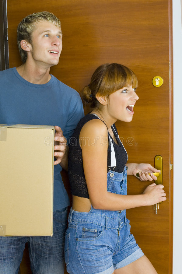 Wow!. Young couple getting in to new flat. They're looking happy and surprised. Man is holding box royalty free stock photos
