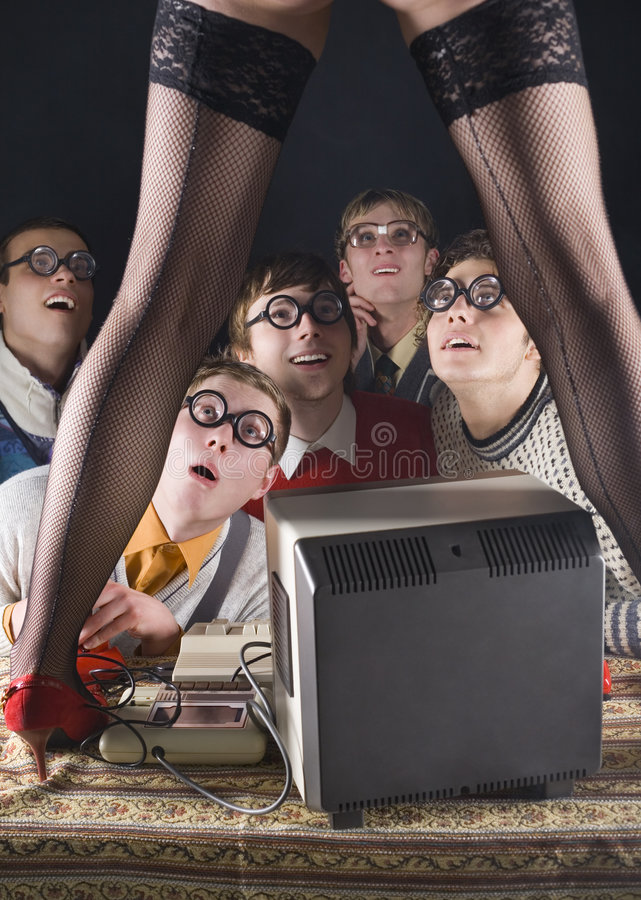 Wow... Five nerdy guys sitting in front of old-fashioned computer and stripteaser. They are looking fascinated. Front view stock image
