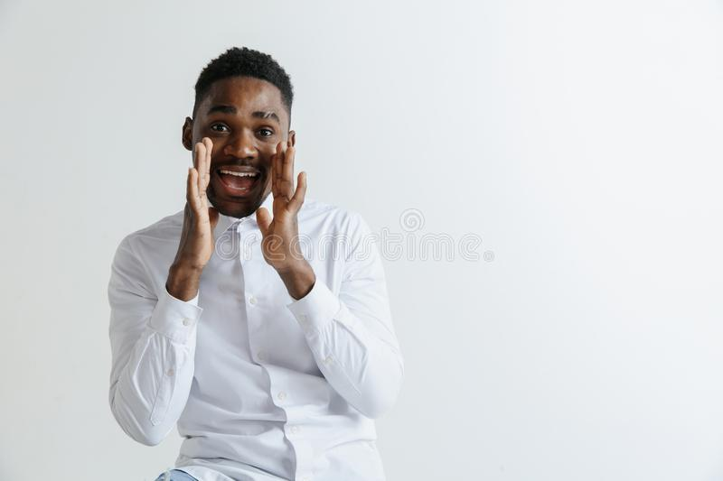 Wow. Attractive male half-length front portrait on grey studio backgroud. Young afro emotional surprised bearded man stock photography