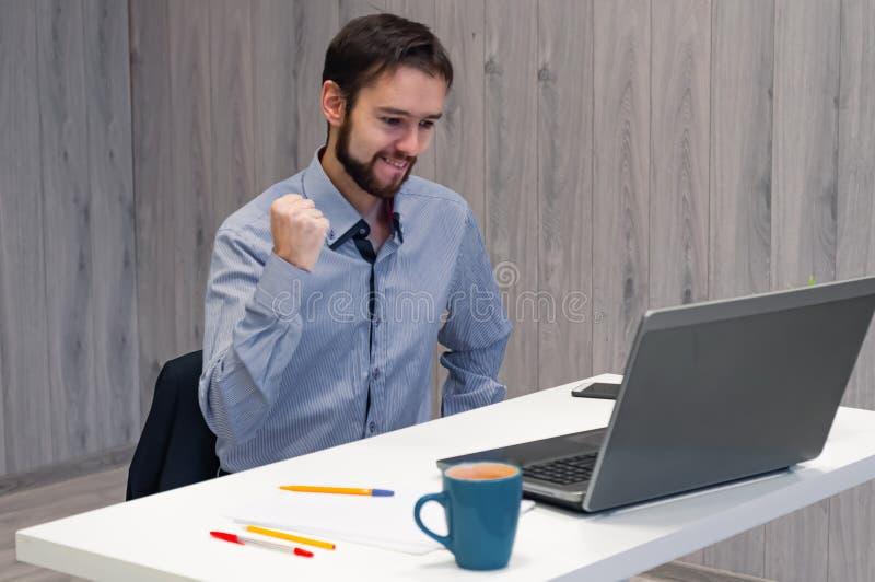 Wow, das ist ein Riesengewinn Junge Geschäftsleute, die sich im Büro aufhalten, Laptop-Display anschauen und lächelnd, Clench-Fäu lizenzfreie stockfotografie
