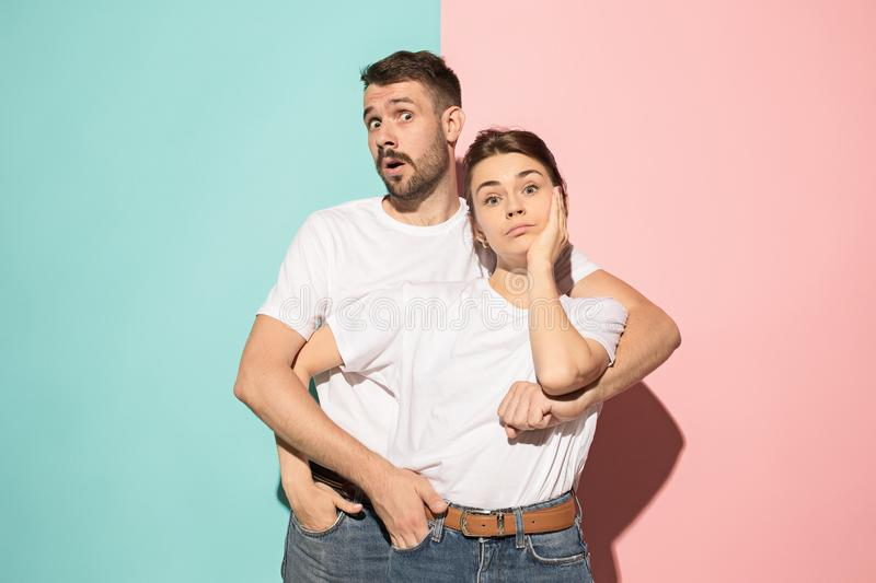 Wow. Doubtful pensive couple with thoughtful expression making choice against pink background royalty free stock image