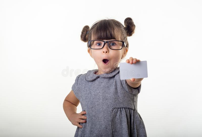 Wow! Happy shocked child holding discount white card in her hands. Surprised kid with credit card. royalty free stock photography