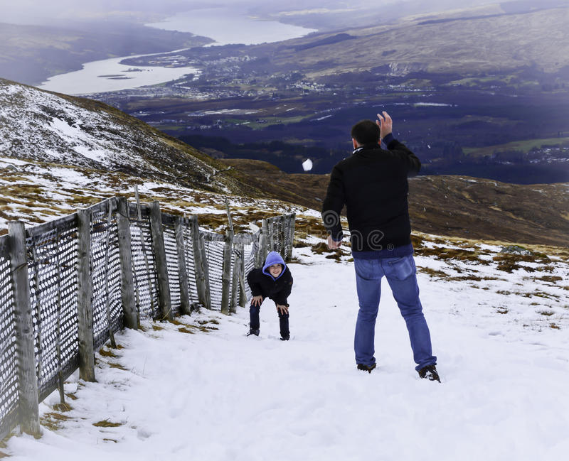 Wow, here comes a snowball. A dad and his son having a snowball fight - picture taken half way up Ben Nevis in Scotland, UK stock photography