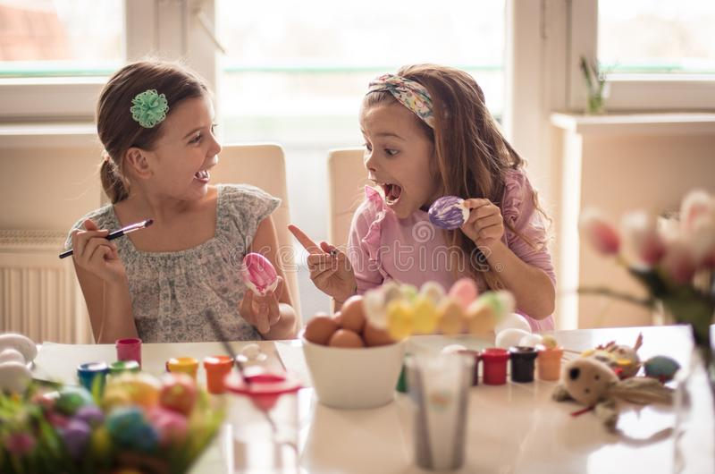 Wow, how nice. Little girls coloring Easter egg stock images