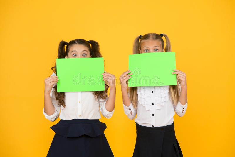 Wow. Little girls holding empty sheets of paper on yellow background. Small children with blank green school paper for. Assignment or project work. Examination stock image