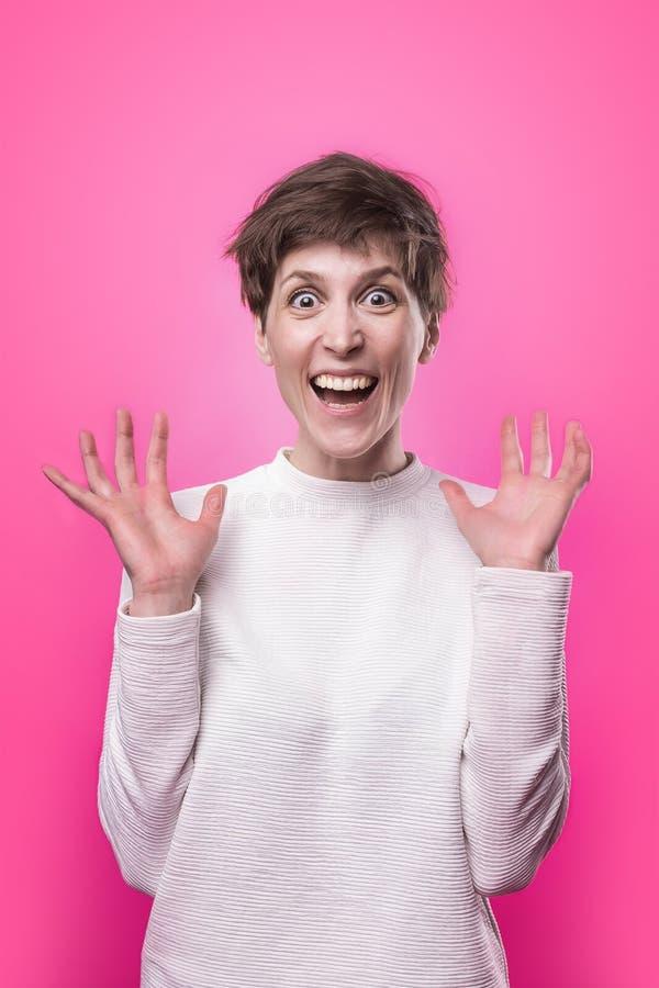 wow Mooi vrouwelijk helft-lengte voorportret dat op roze studio wordt geïsoleerd backgroud stock afbeelding