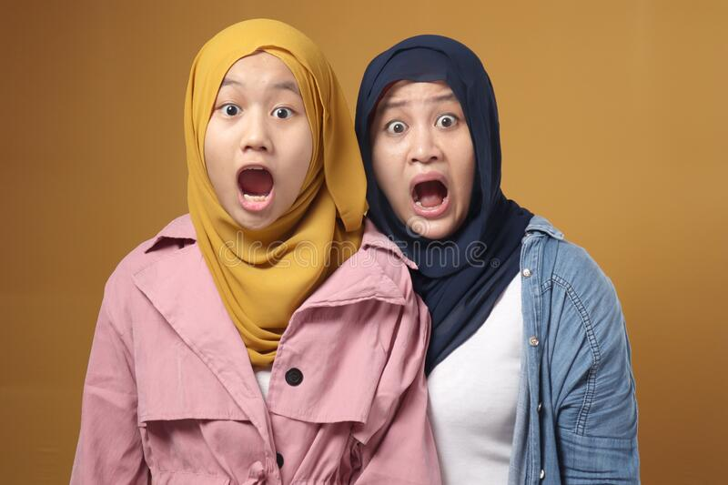 Wow omg unbelievable. Beautiful Asian muslim family of mother and daughter together afraid and shocked with surprise expression stock image