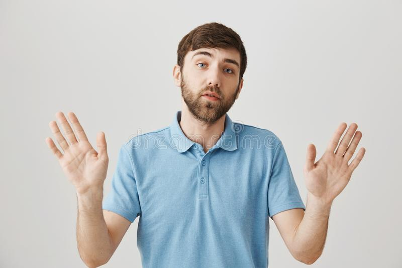 Wow, slow down. Studio shot of calm and serious caucasian guy standing with raised palms and worried expression, trying stock photography