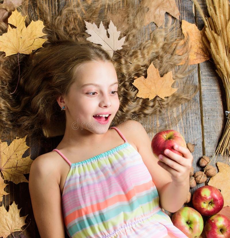 Wow. Small girl likes the taste of apple fruits. Cute girl child with ripe autumn crops. Organic and natural food for royalty free stock images