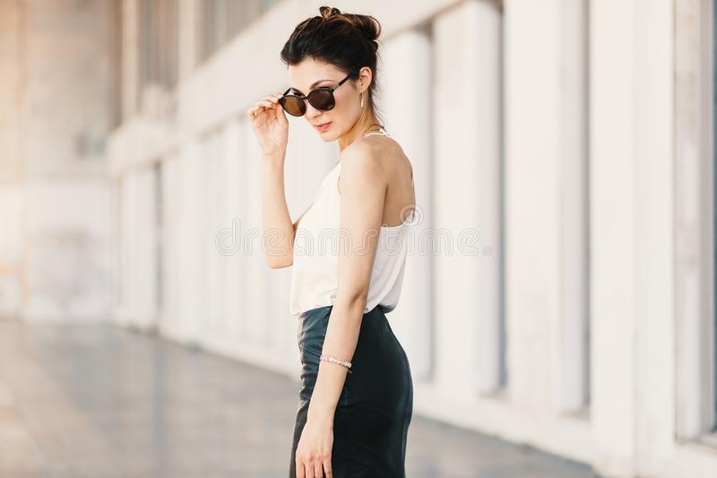 Refined business woman holding fashionable sunglasses down looki stock image