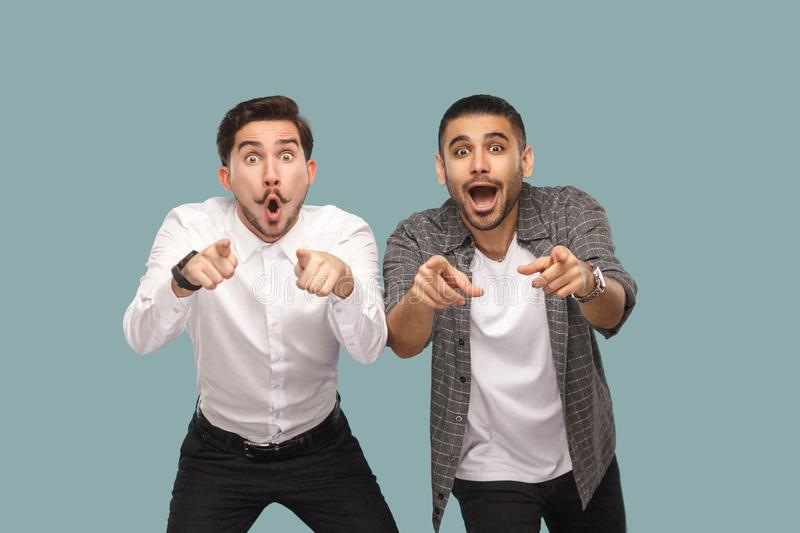 wow, are you serious? two surprised pointing finger handsome bearded friends standing and looking at camera with open mouth and b royalty free stock image