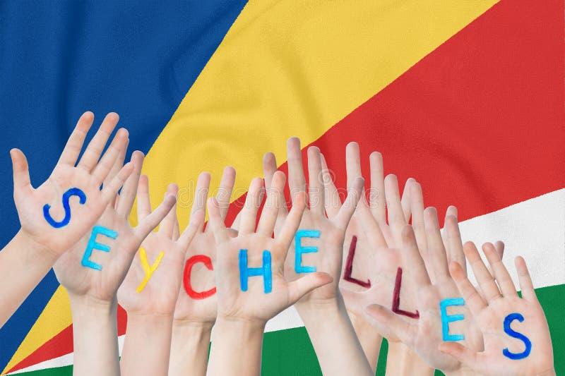 Wpisowi Seychelles na dziecko rękach przeciw tłu falowanie flaga Seychelles obrazy royalty free