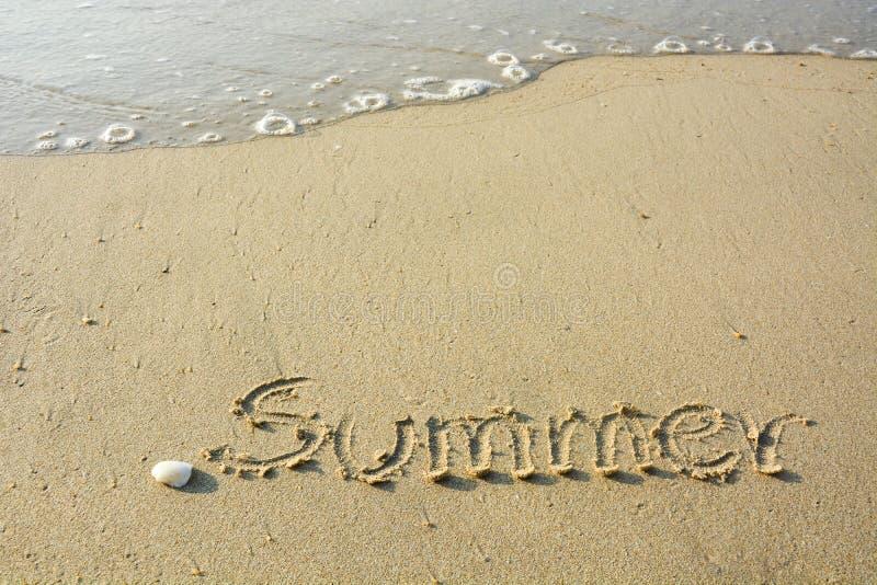 Wpisowy «lato «handwriting i skorupą na plażowym piasku z miękkim światłem słonecznym w wieczór i falą zdjęcie stock