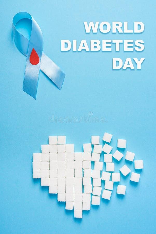 Wpisowy światowy cukrzyca dzień, błękitnego faborku świadomość z czerwoną krwi kroplą, złamane serce cukrowi sześciany, błękitny  obraz stock