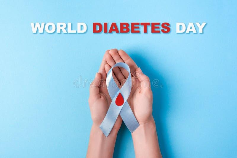 Wpisowy światowy cukrzyca dzień i błękitnego faborku świadomość z czerwoną krwi kroplą w kobiet rękach na błękitnym tle zdjęcia royalty free