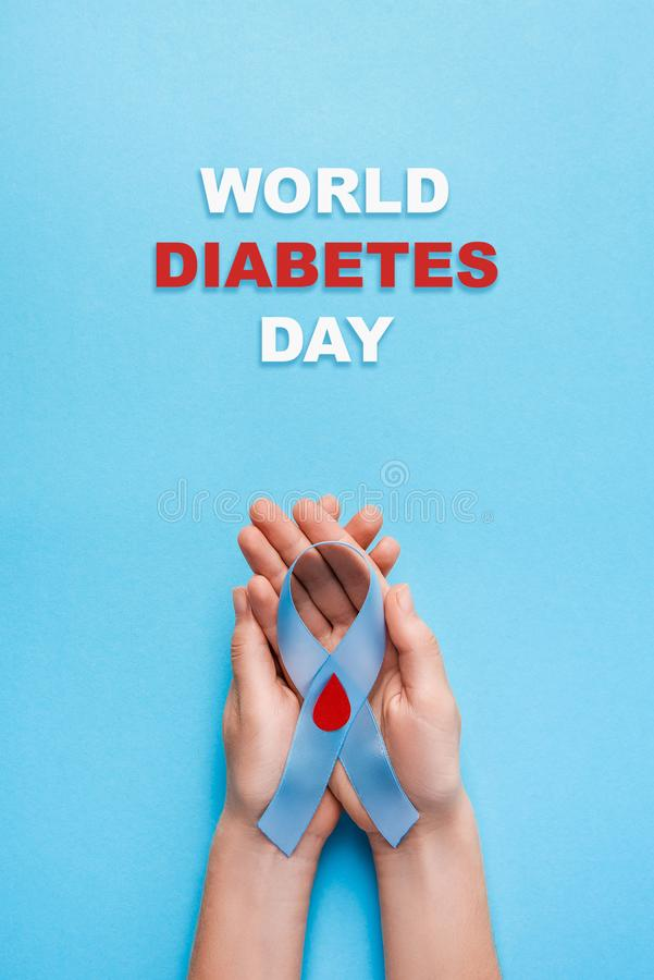 Wpisowy światowy cukrzyca dzień i błękitnego faborku świadomość z czerwoną krwi kroplą w kobiet rękach na błękitnym tle obrazy stock