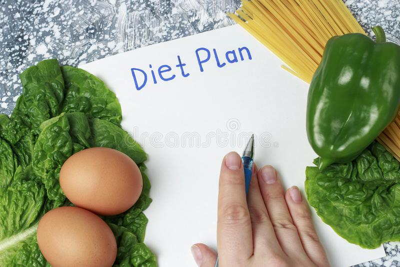 Wpisowy dieta plan na bielu szkotowym i zdrowym jedzeniu, pisze r?ce na widok fotografia royalty free