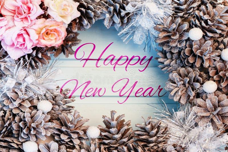 Wpisowy Szczęśliwy nowy rok na błękitnym drewnianym tle, Bożenarodzeniowy przygotowania rożki i kwiaty, rama fotografia royalty free