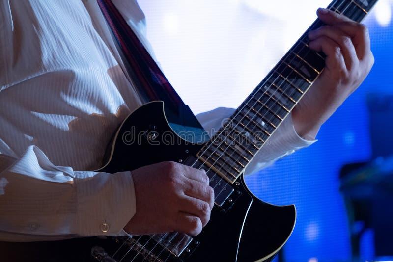 Wręcza gitarzysty na sznurkach Mężczyzna w biel koszula bawić się czarną gitarę elektryczną muzykalny temat niebieska tła zdjęcia royalty free