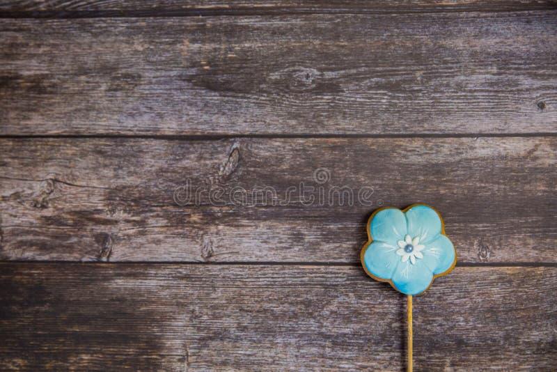 Wręcza malującego piernikowego błękitnego kwiatu na drewnianym tle Odgórny widok Słodki deser jako prezent dla kobieta dnia na 8  zdjęcia stock