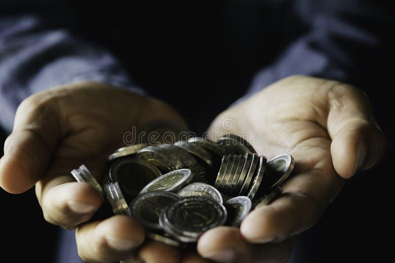 Wręcza mienie pieniądze złociste monety z rośliną w ręce dla pieniężnego i oszczędzania pieniądze pojęcia zdjęcie stock