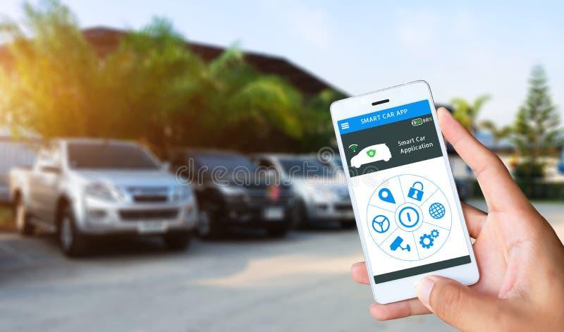 Wręcza trzymać mądrze zastosowanie deskę rozdzielczą z plama parking samochodowym tłem i telefon obraz royalty free