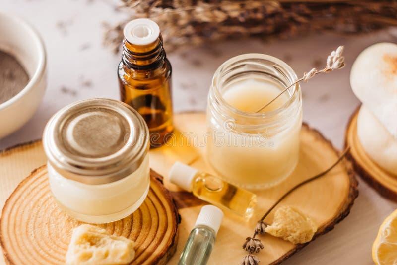 Wręcza śmietanki i wargi balsam w szklanym słoju Naturalni organicznie kosmetyki z miodem, woskiem i olejami, zdjęcie royalty free