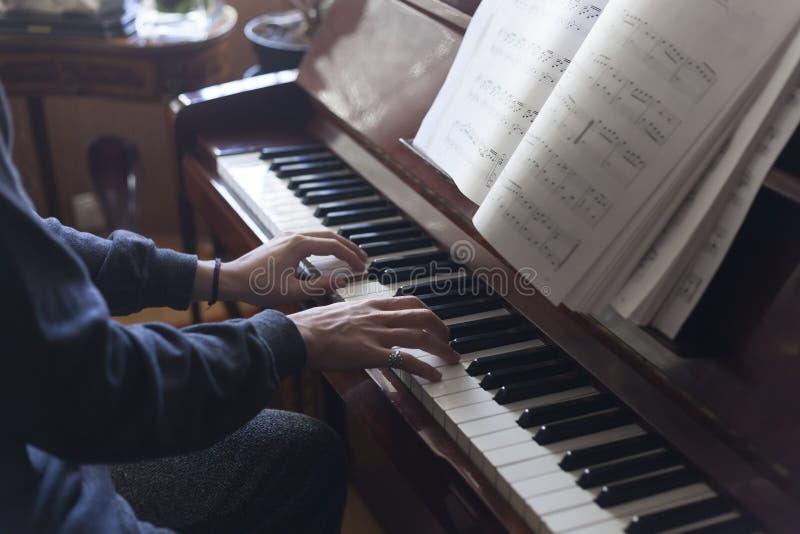 Wręcza bawić się pianino podczas gdy czytający muzycznych prześcieradła fotografia stock