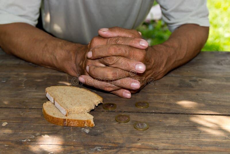 Wręcza biednego starego człowieka ` s, kawałek chleb i zmianę, centy na drewnianym tle Pojęcie głód lub ubóstwo zdjęcie stock