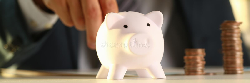 Wręcza biznesmena stawia wałkowego pieniądze w świnię zdjęcia stock