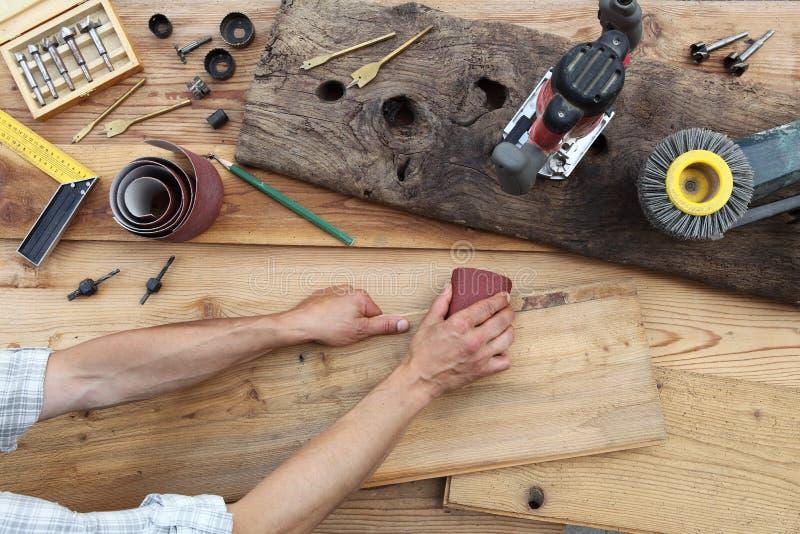 Wręcza cieśli pracuje drewnianą nieociosaną starą deskę z piaska pa obrazy stock