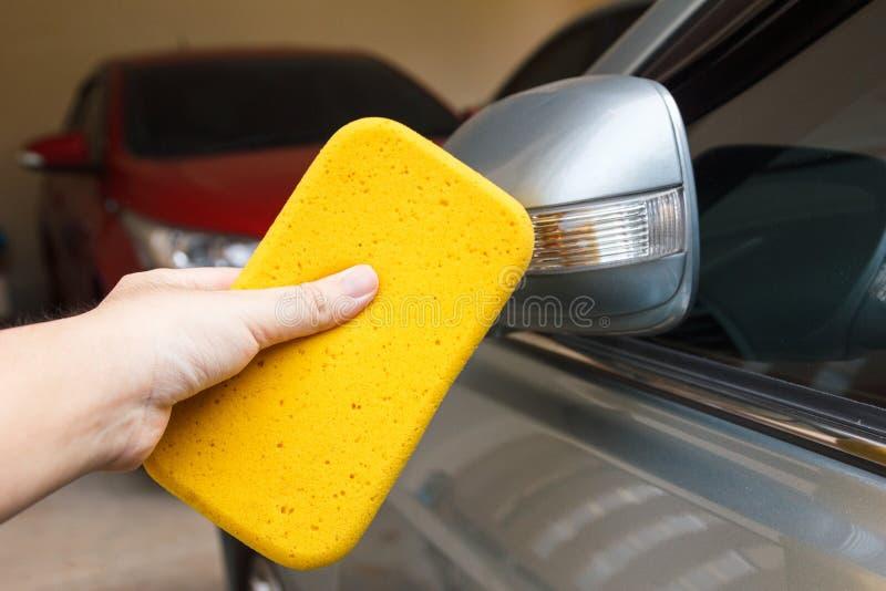 Wręcza cleaning samochodowego ` s brud z gąbką zdjęcie stock